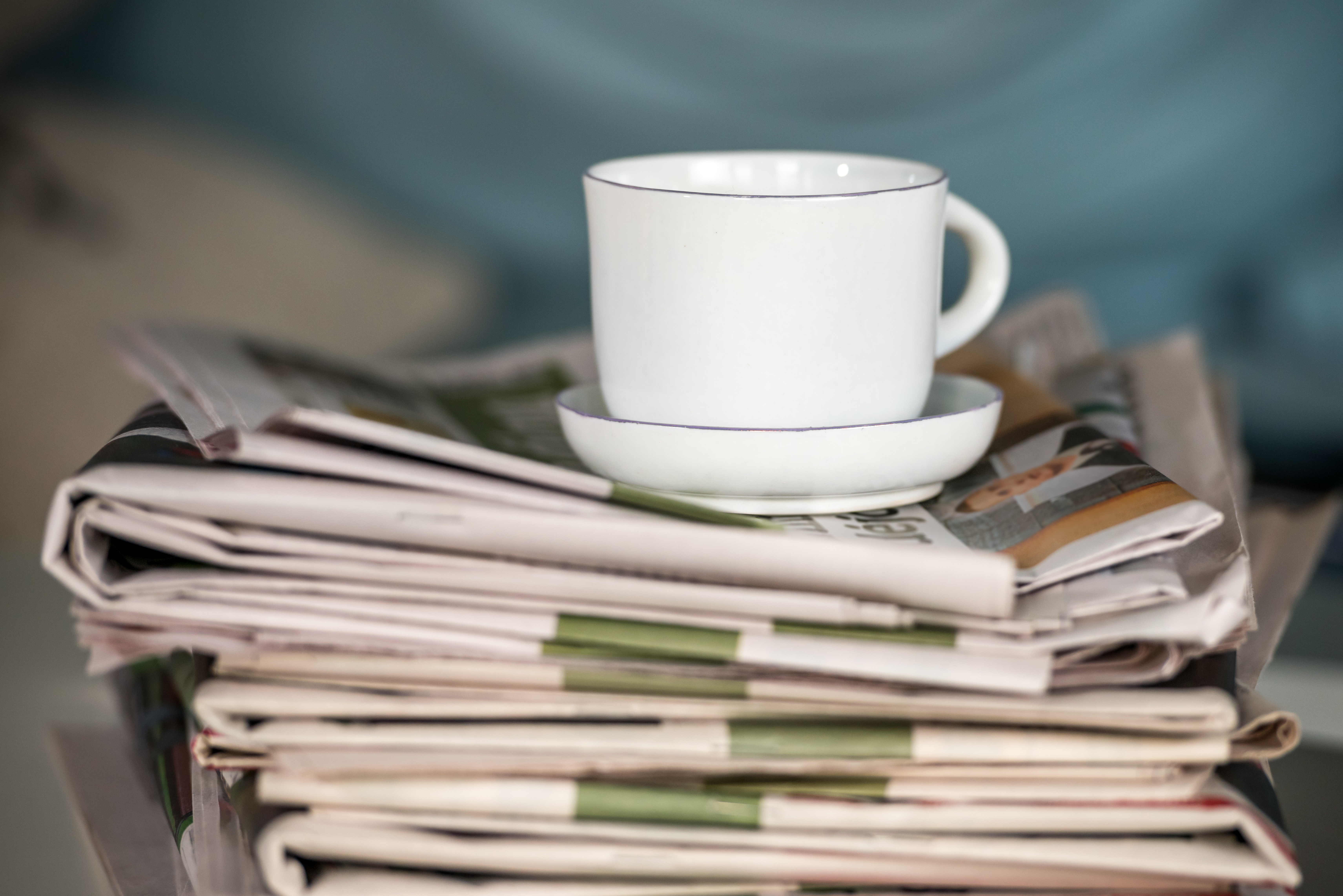 Stack of newspaper and coffee cup
