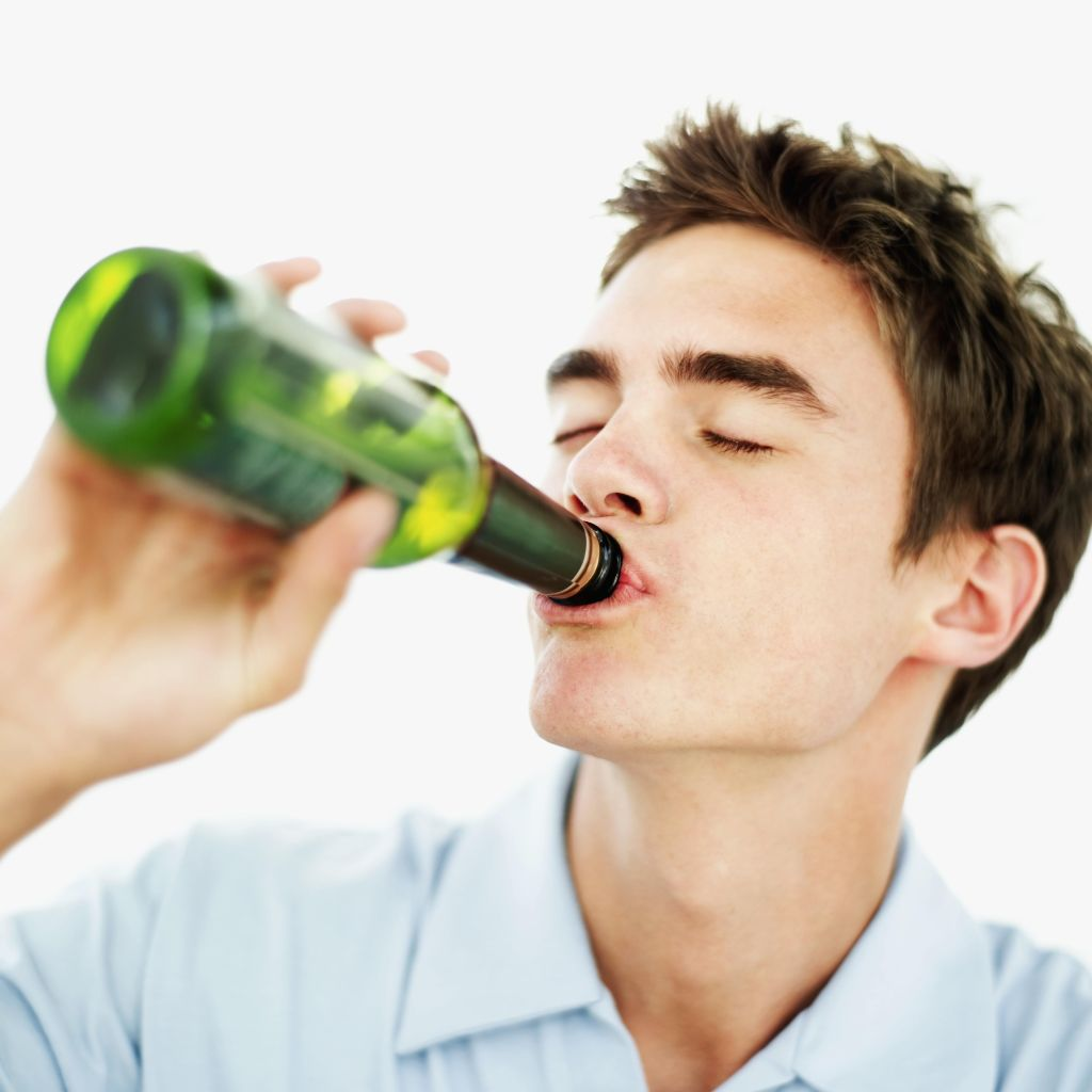 close-up of a teenage boy drinking a bottle of beer