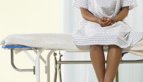 Female patient sitting on gurney in hospital gown, low section