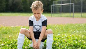 Serious boy sitting on football