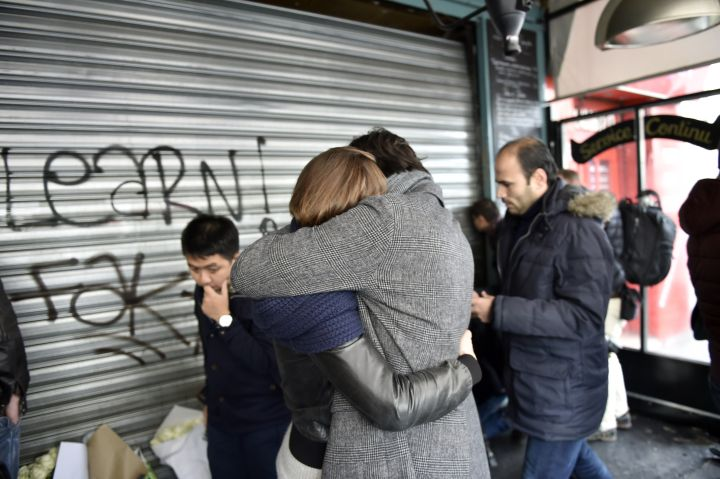 Two friends hug in the wake of multiple terror attacks in Paris.
