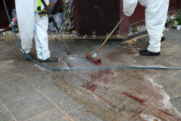Workers wash blood off of the floor outside of Le Carillon bar.