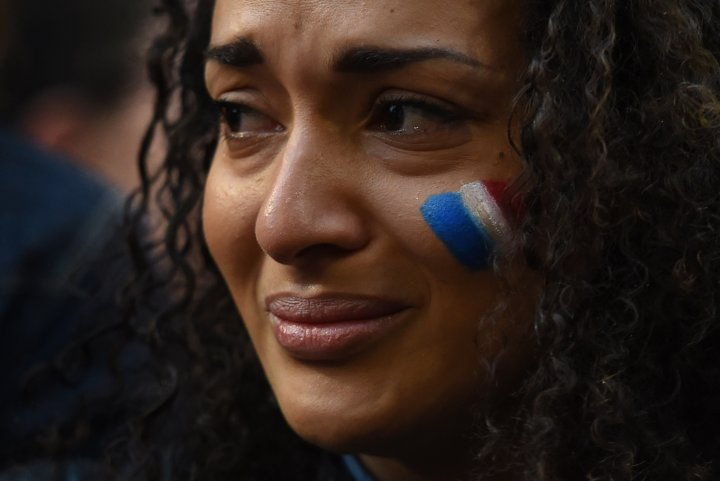 A young woman cries at a vigil held by a local French community in Sydney.