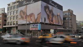 Cars drive past a billboard featuring Is