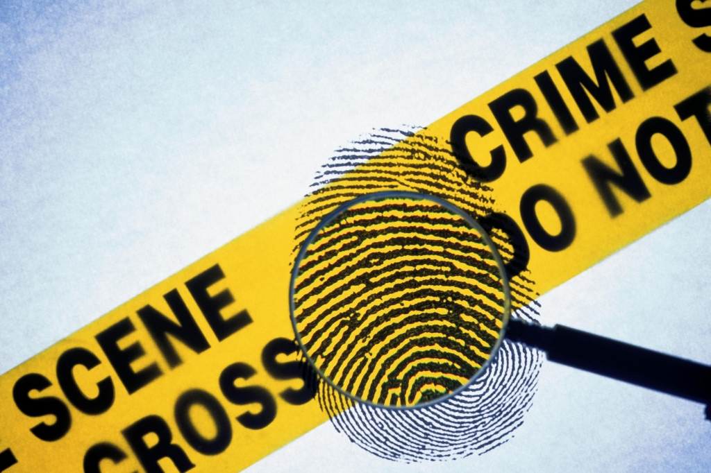 Police tape with fingerprint and magnifying glass
