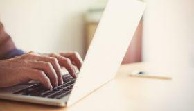 Senior man typing on laptop at table