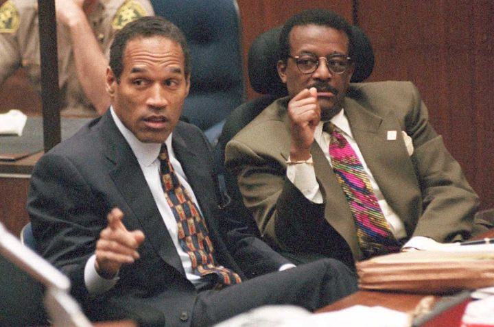 Murder defendant O.J. Simpson (L) points towards p