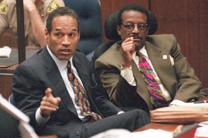 Murder defendant O.J. Simpson (L) points towards p