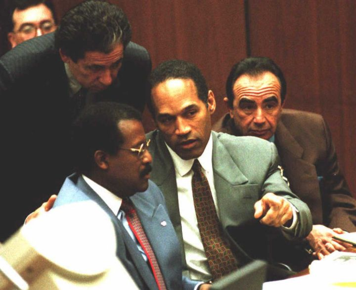 O.J. seen talking to his lawyers Robert Shapiro, Johnnie Cochran, and Robert Kardashian during a trial date.