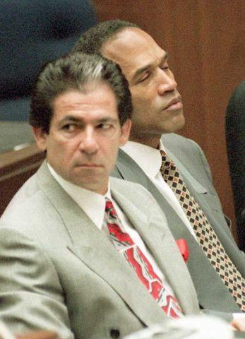 Murder defendant O.J. Simpson (R) listens to testi