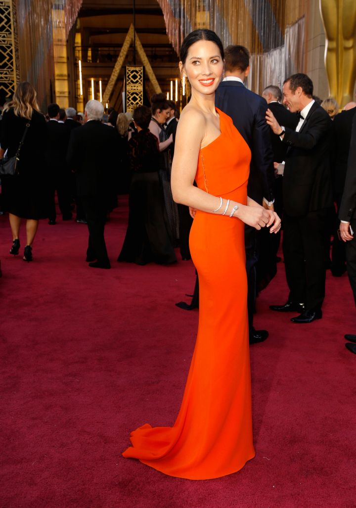 Olivia Munn is all smiles in a bright, orange gown.