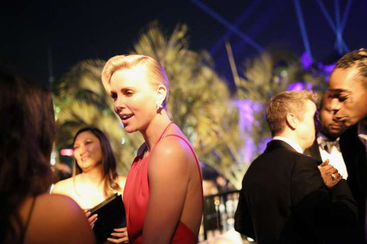 Wiz Khalifa appears to be enjoying the views of the room as Charlize Theron chats at the Vanity Fair after party.