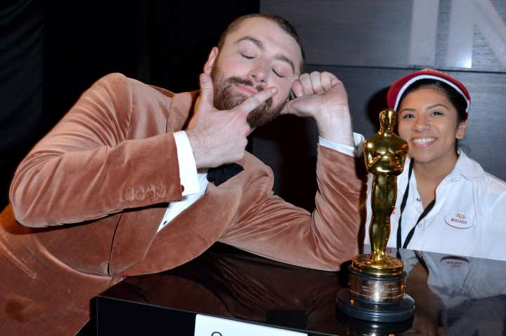 Sam Smith shares a moment with a worker at the Oscars After Party