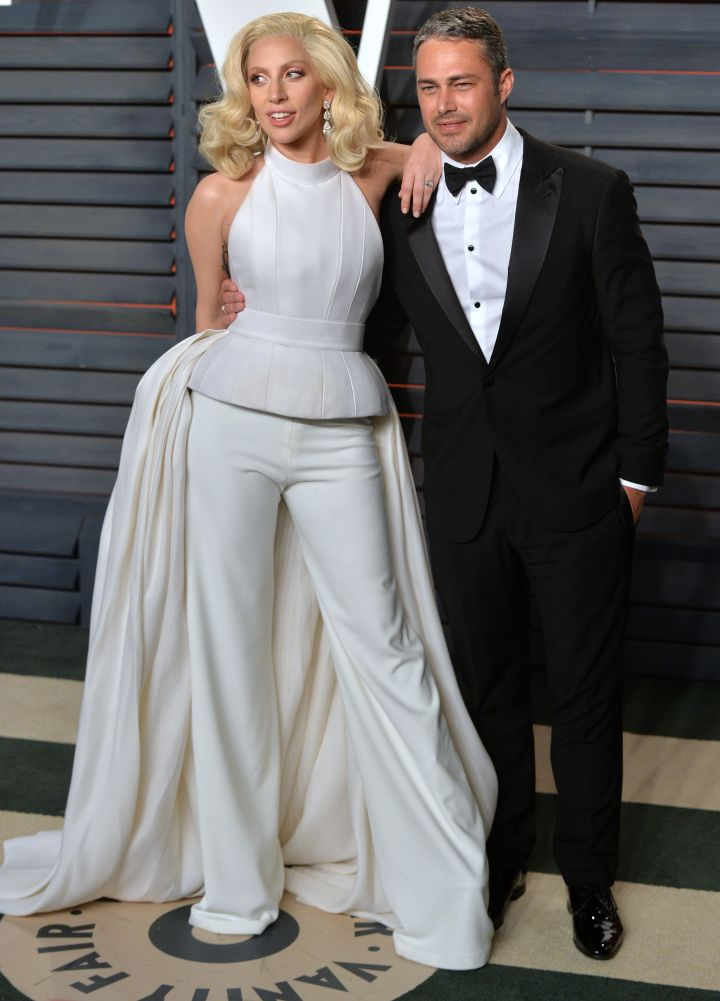 "Lady Gaga chose to wear yet another ""gown suit"" as she posed with her boyfriend Taylor Kinney."