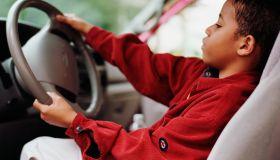 African boy pretending to drive car