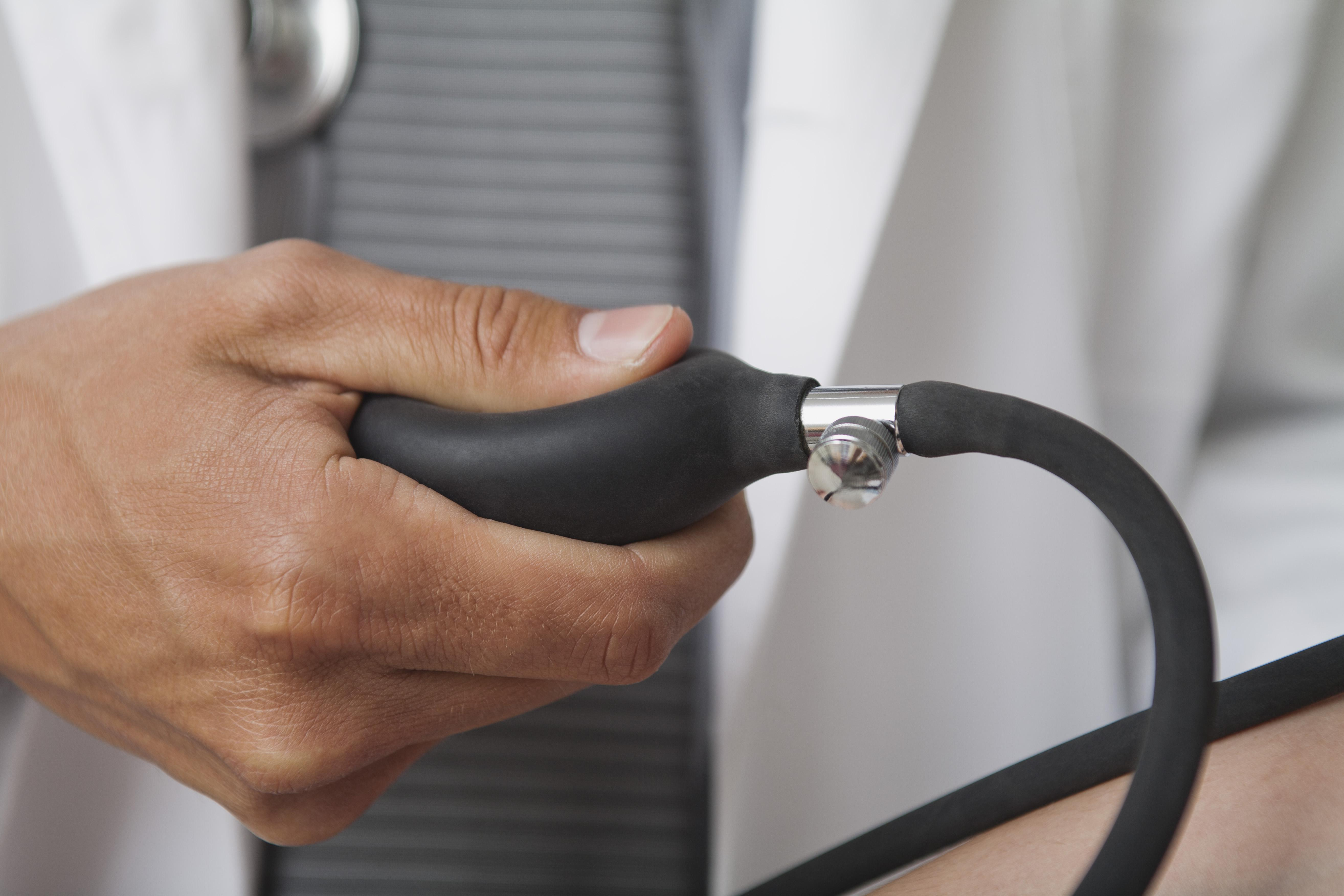 Doctor squeezing bulb on blood pressure gauge, cropped