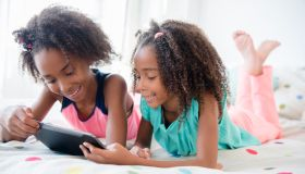 Mixed race sisters using digital tablet on bed
