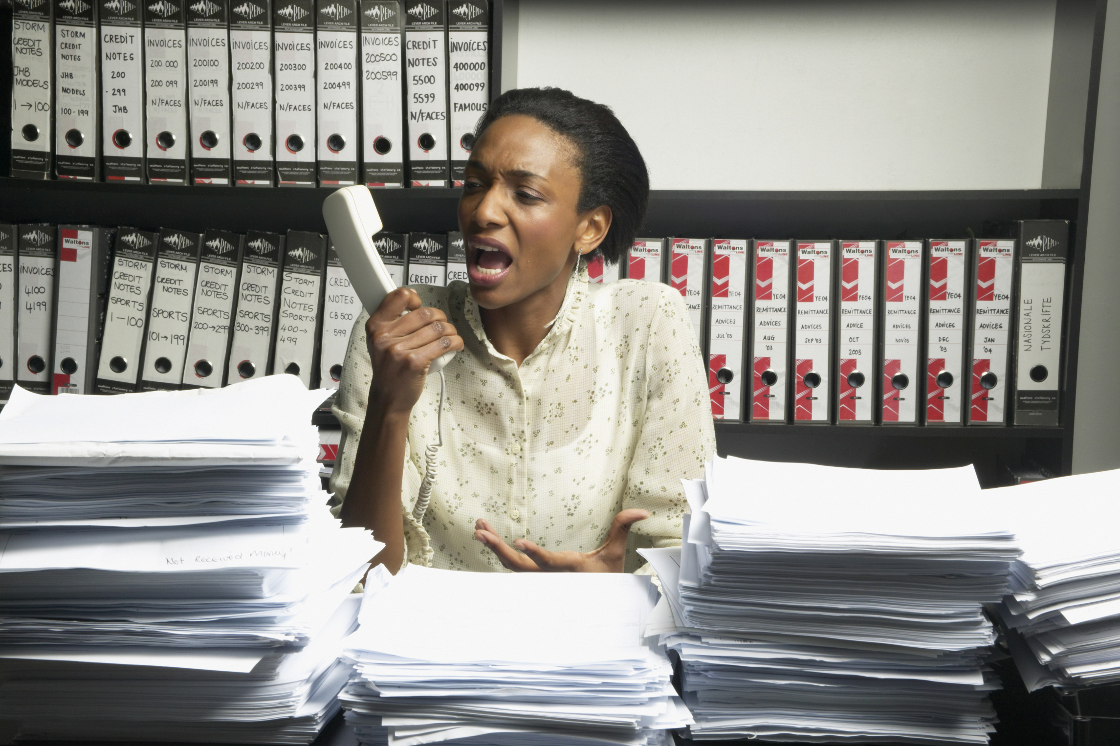 Female office worker at desk screaming into telephone receiver