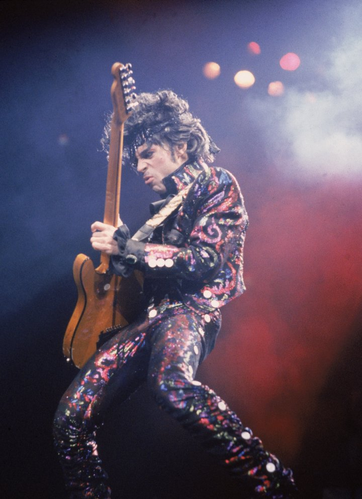 Prince plays guitar on stage during a concert, 1985.