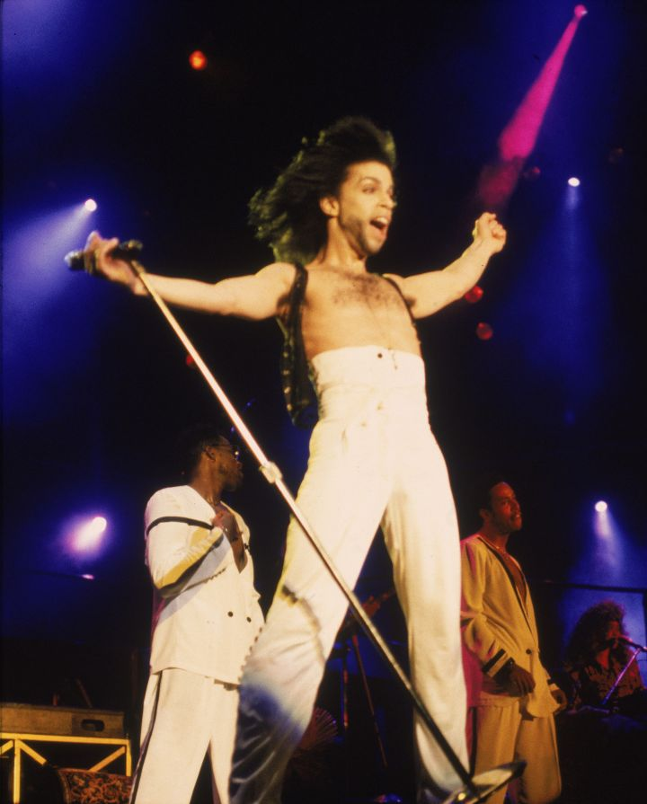American singer and songwriter Prince stands on stage with his arms outstretched, wearing high-waisted white pants, circa 1990.