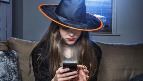 halloween witch checking her mobile phone.