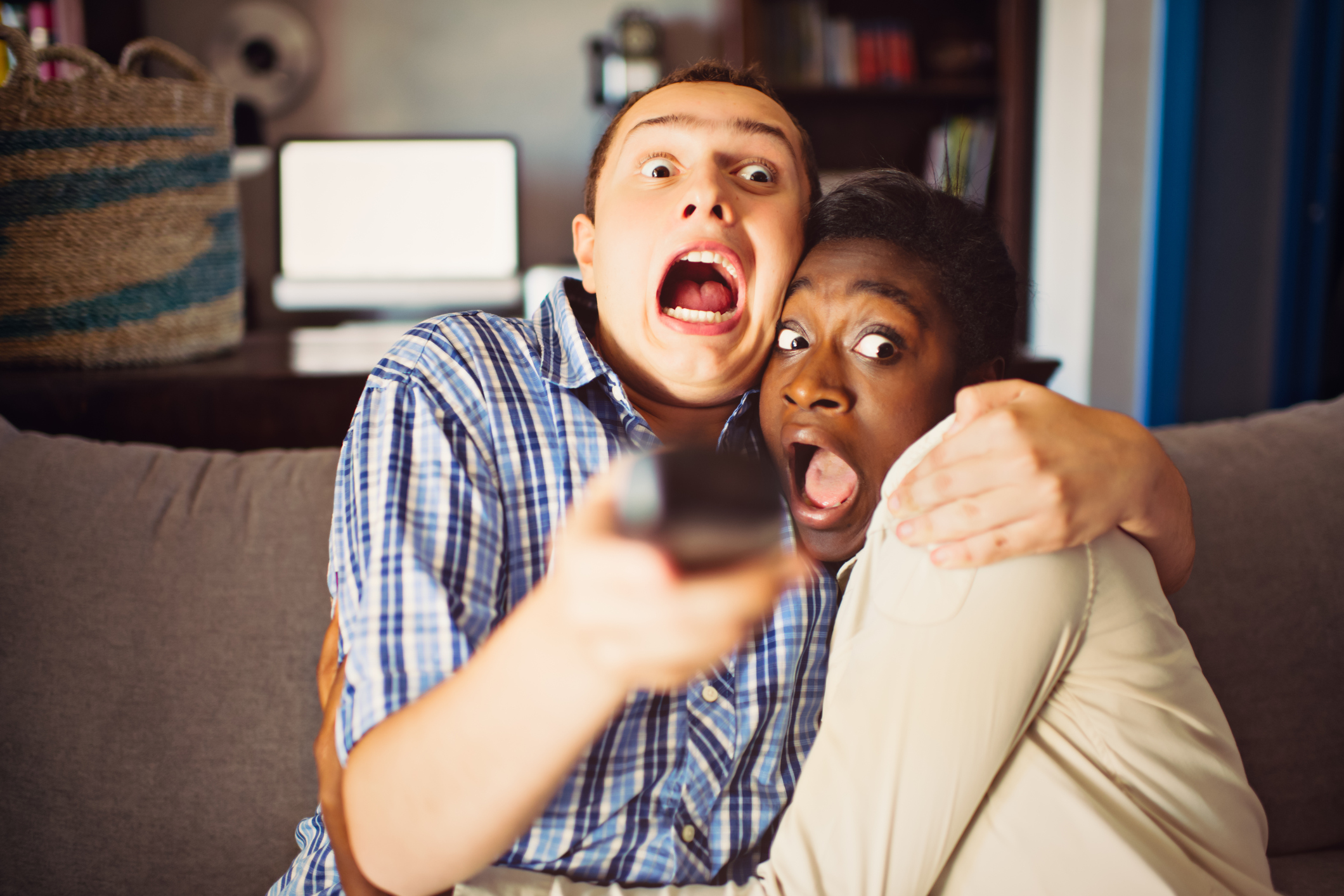 Mixed race teenage couple watching a movie at home