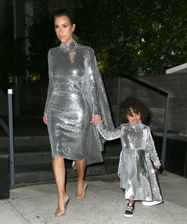 Kim Kardashian takes North West to see her father Kanye West perform in matching silver sequined outfits.