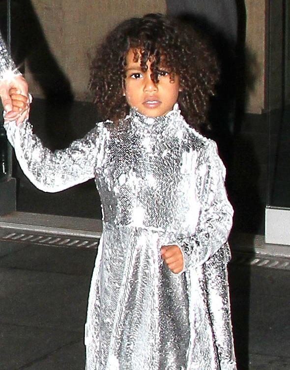 North West learning the family business in her silver sequins.