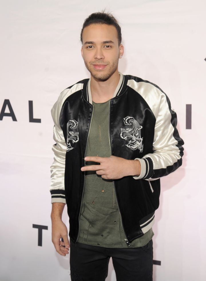 Prince Royce chucks up the deuces.