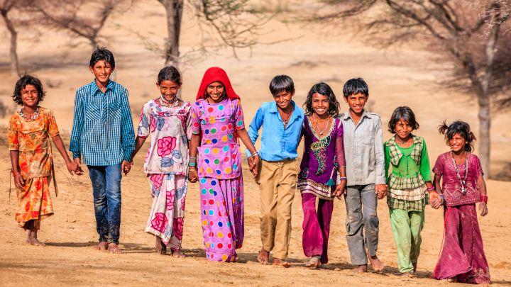 Group of happy Indian children walking across sand dunes, India