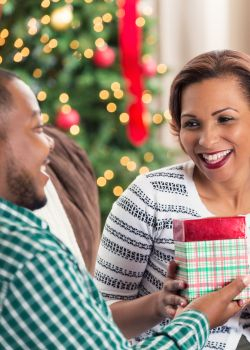 African American couple opening gift on Christmas morning