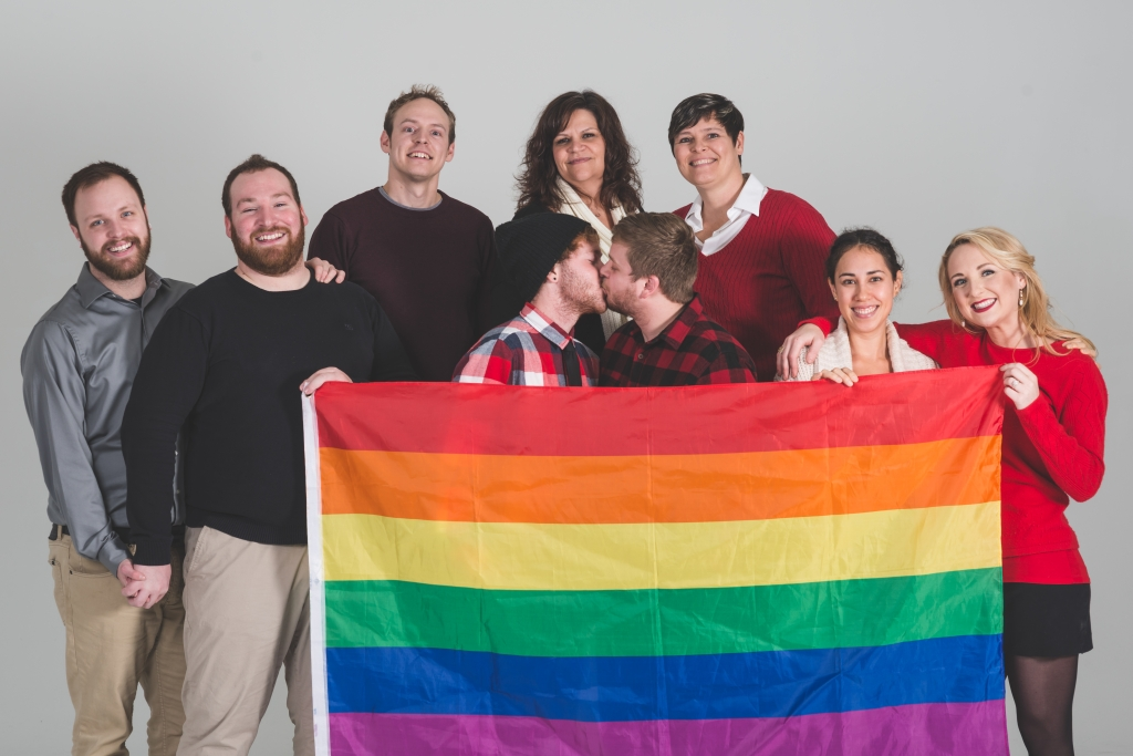 Group of LGBT advocates holding pride flag