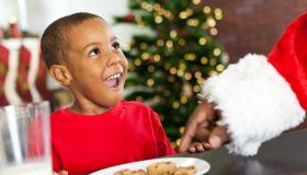 Surprised little boy sees Santa taking Christmas cookie