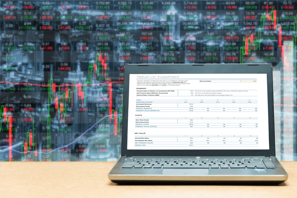 Laptop with investment screen on table with stock exchange market business trading graph. Business marketing trade concept.