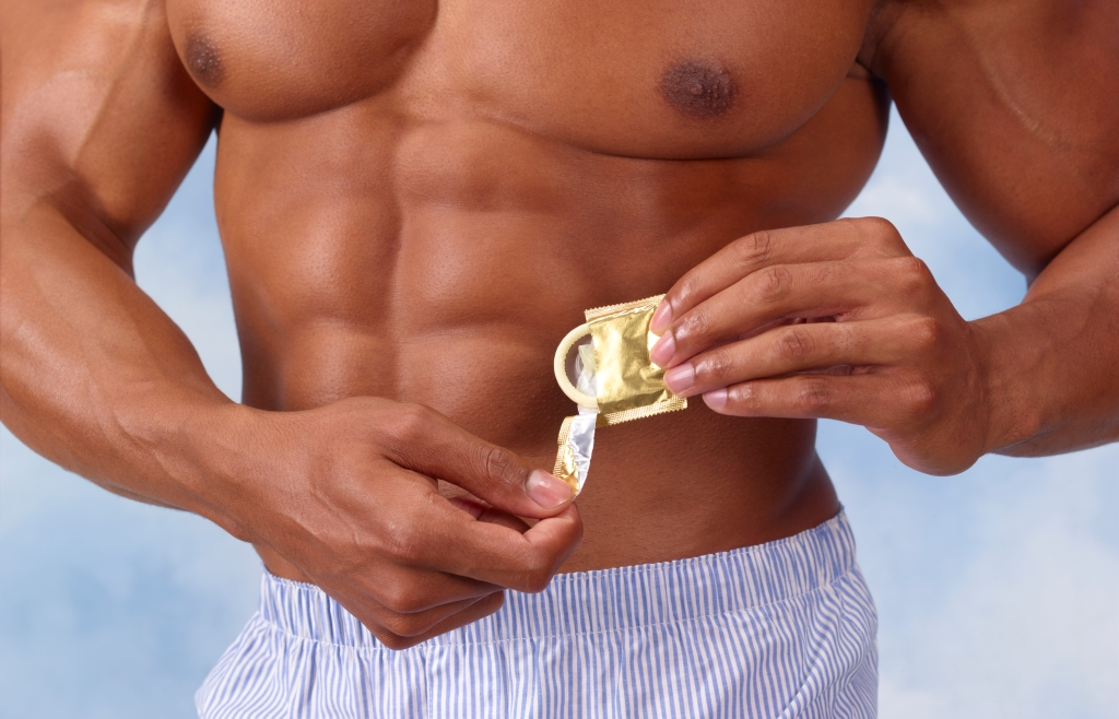 muscular man opening condom packet