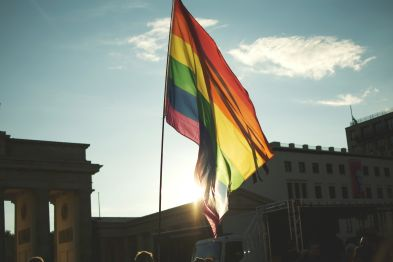 Low Angle View Of Rainbow Flag At Brandenburg Gate Against Sky
