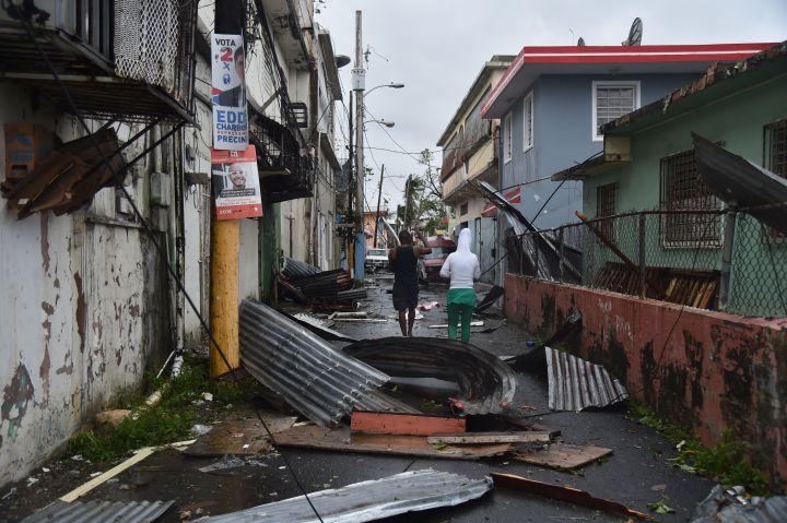 San Juan, PR: Residents walk past damaged homes following Hurricane Maria.