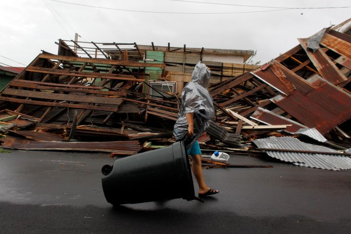 Fajardo, PR: A woman pulls a trash can past a destroyed home.