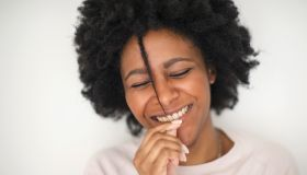 Smiling Black woman playing with hair