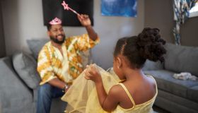 Man casting spell on daughter in fairy costume in living room