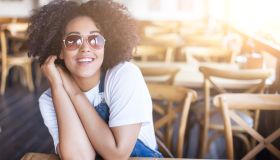 Smiling african woman sitting in sunny cafe