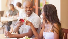 Cheers celebrating and toasting happy african couple having lunch