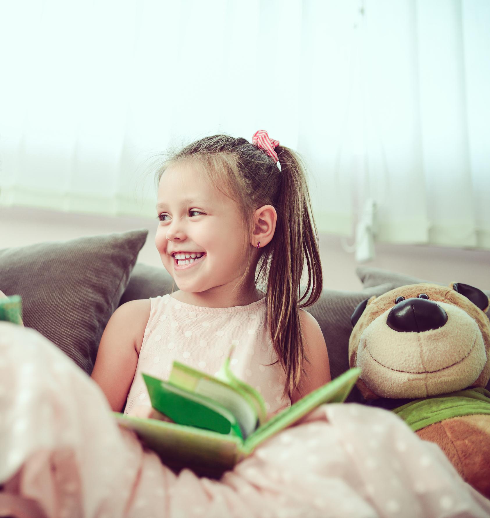 Smiling Toddler Girl Reading Book To Toy Bear