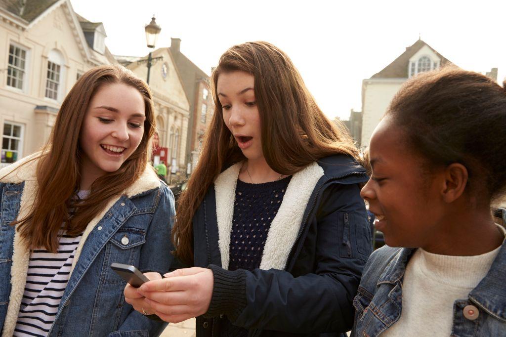 Teenage Girls Walking Along Street Looking At Social Media