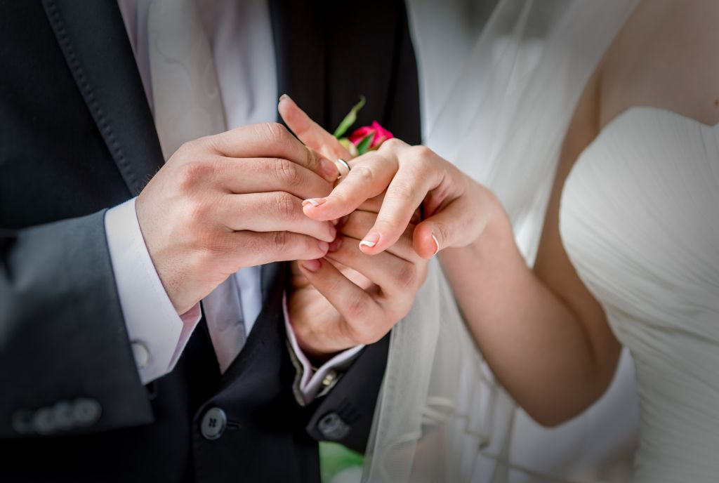 Midsection Of Groom Putting Ring In Bride Finger At Wedding