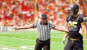 American football referee signals a play during the game. Player.