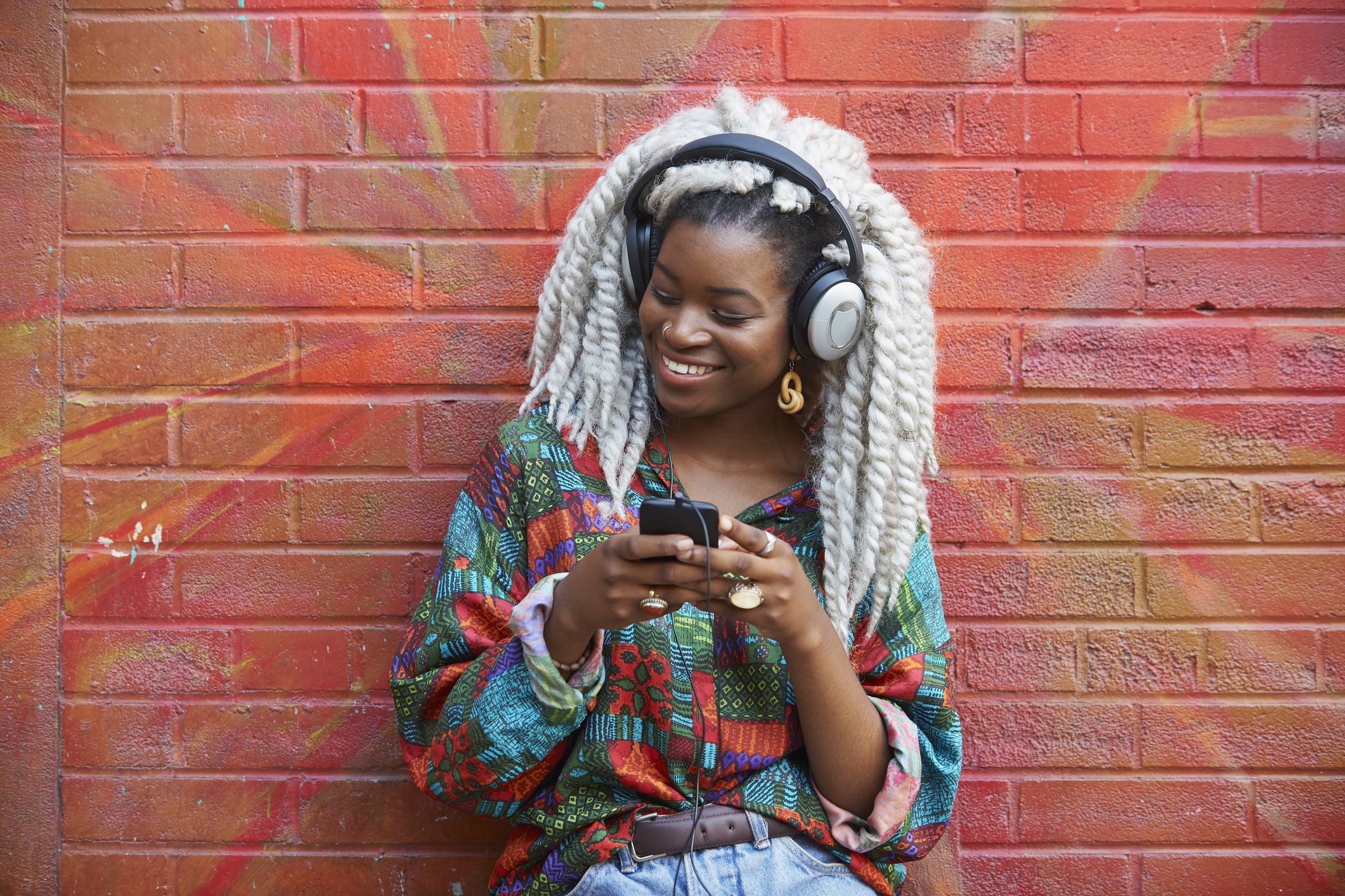 Black woman leaning on brick wall listening to cell phone with headphones
