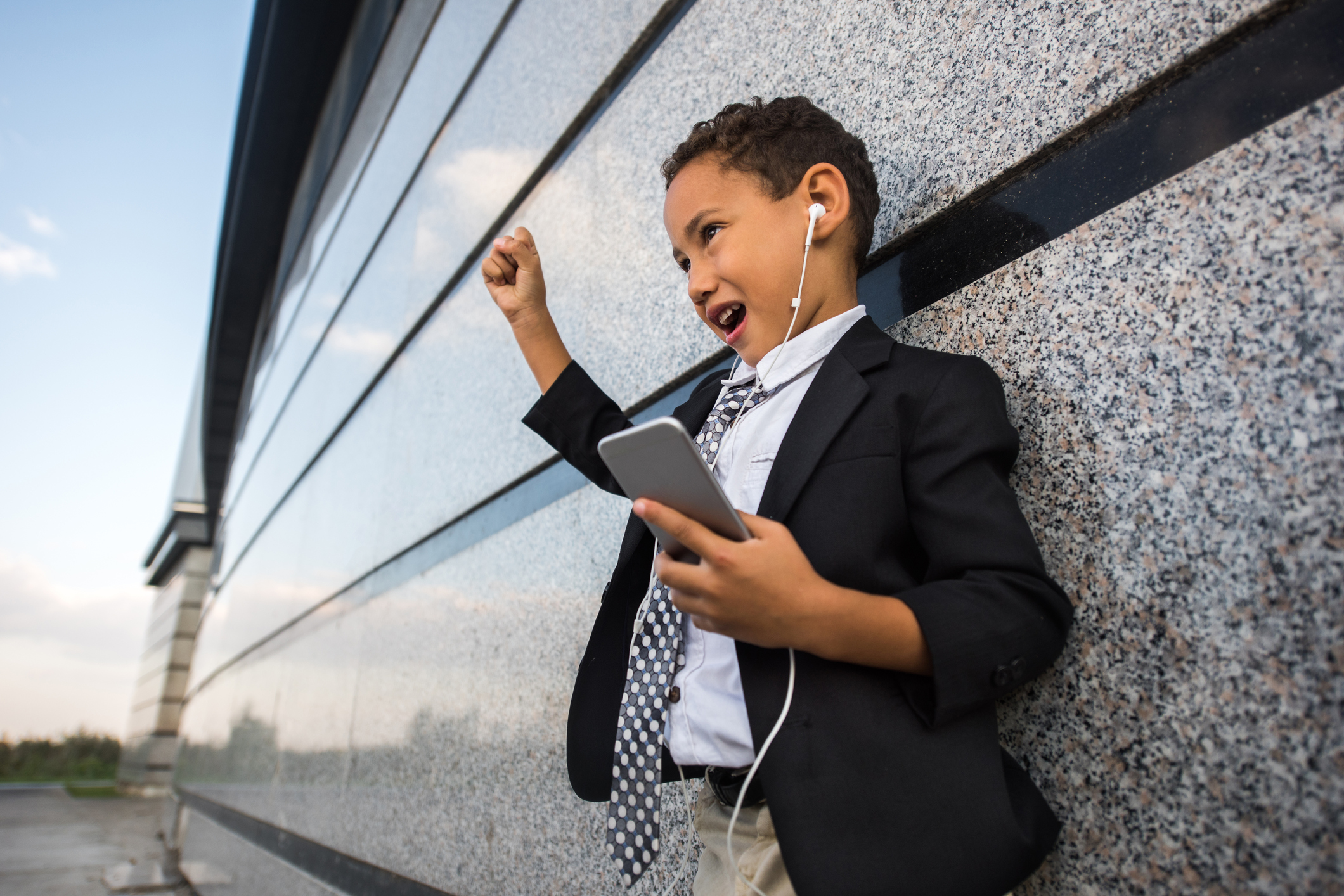 Small African American business boy singing while listening MP3 player.