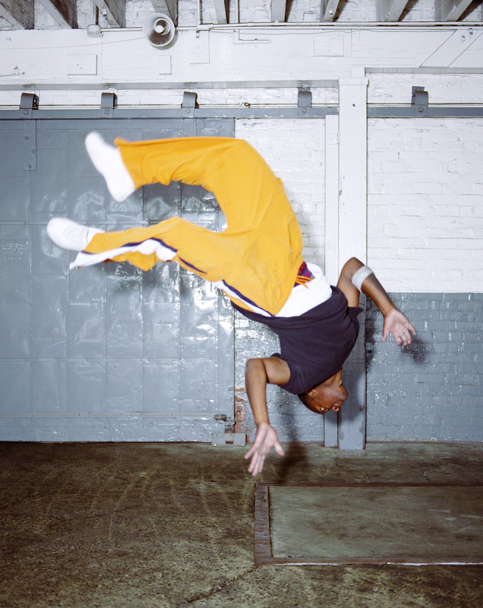 Young male breakdancer doing backflip (blurred motion)