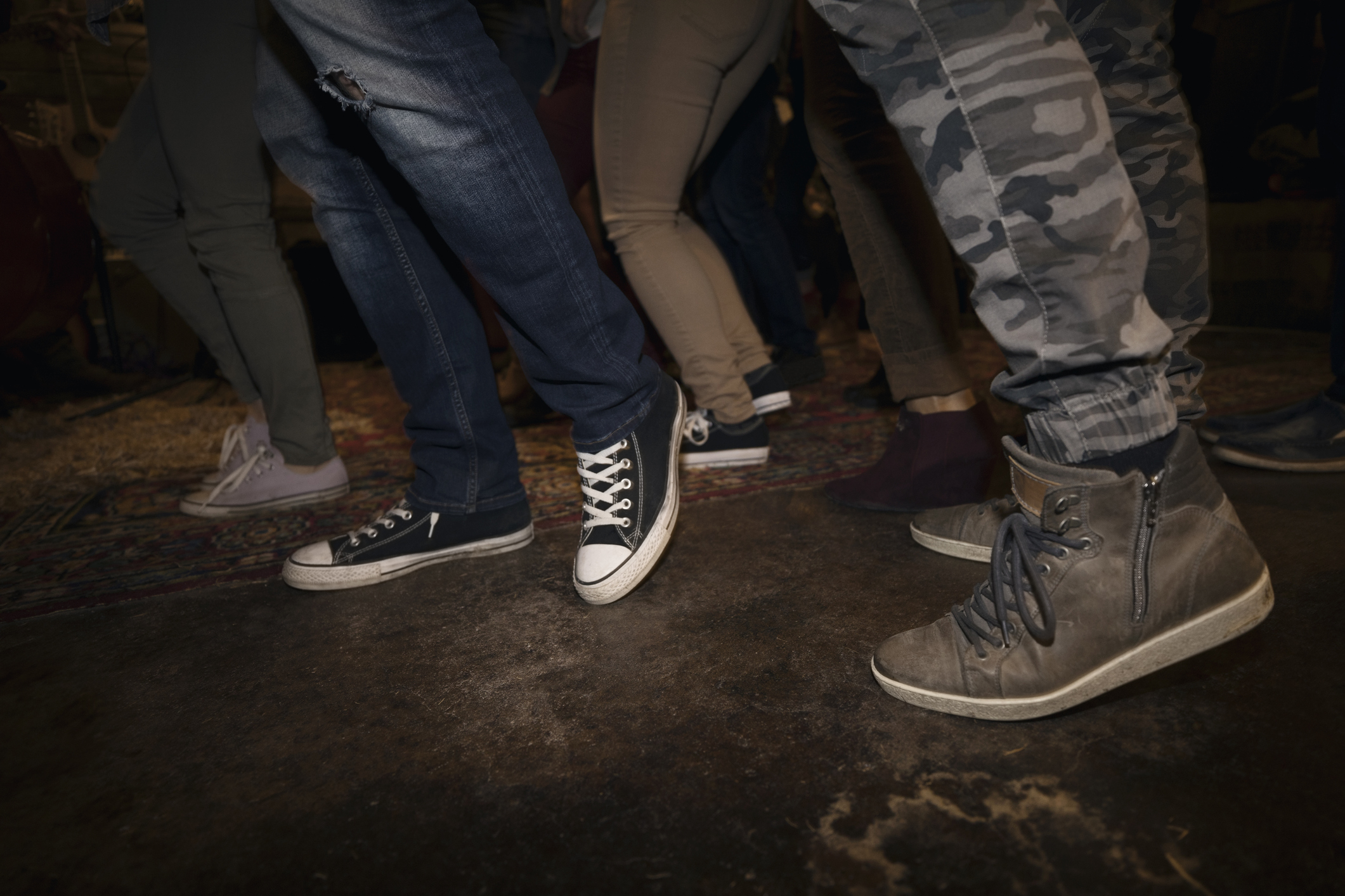 Legs of young friends dancing at party